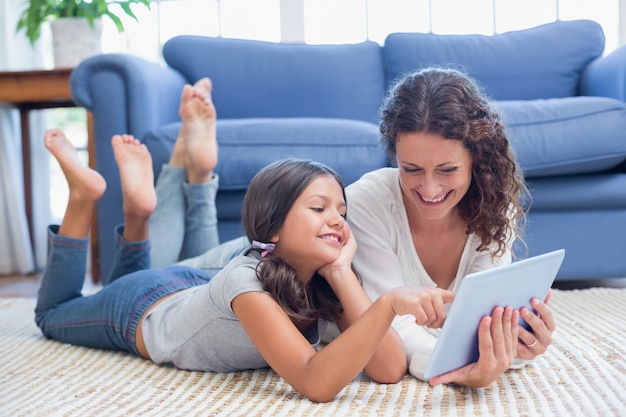 Happy mother and daughter lying on the floor and using tablet