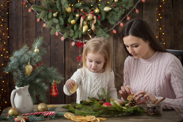 Happy mother and daughter make  christmas wreath