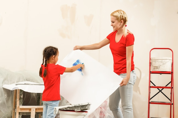Happy mother and daughter painting a wall at home