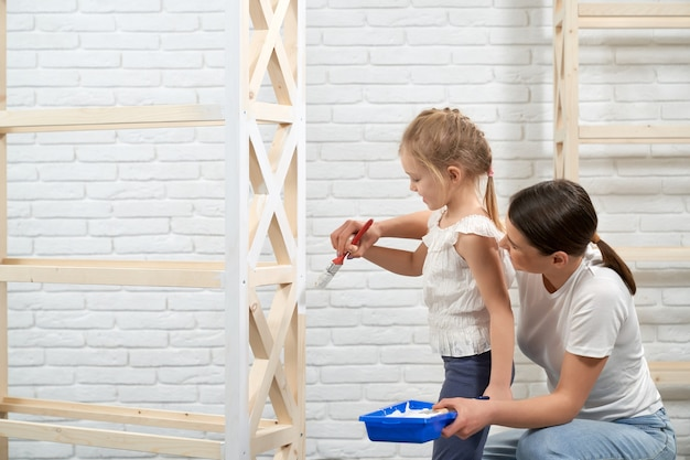 Happy mother and daughter painting wooden shelves