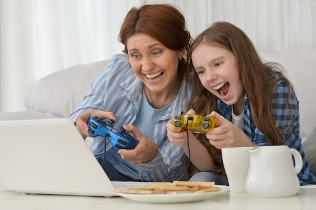 Happy mother and daughter playing computer games on laptop