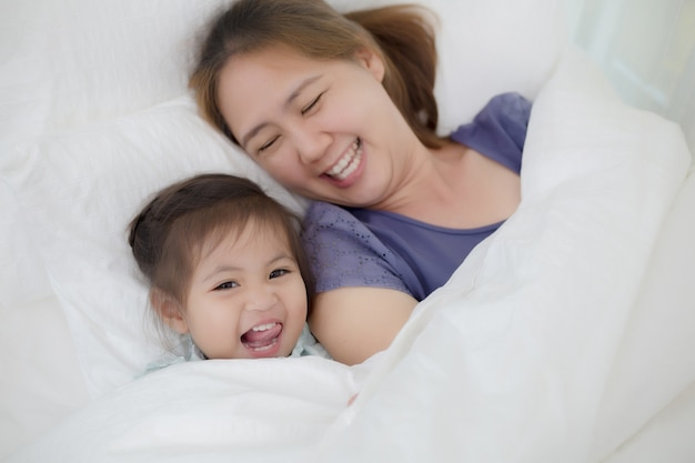 Happy mother and daughter playing hide and seek in bed room
