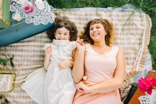 Happy mother and daughter playing and smiling while lying on a blanket in the summer