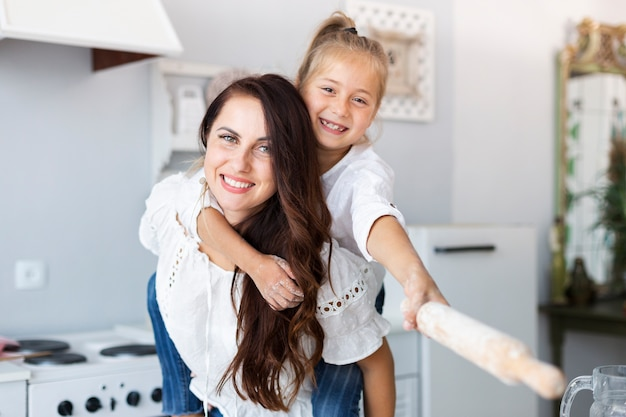 Happy mother and daughter posing with kitchen roller