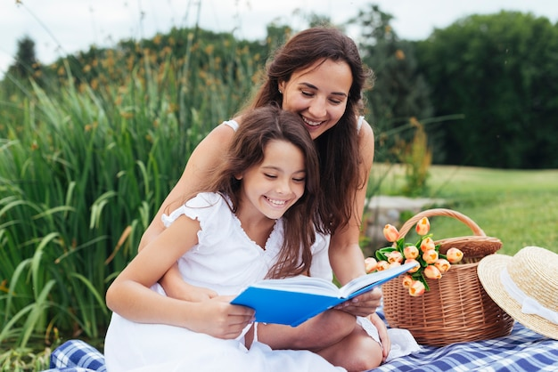Happy mother and daughter reading book at picnic