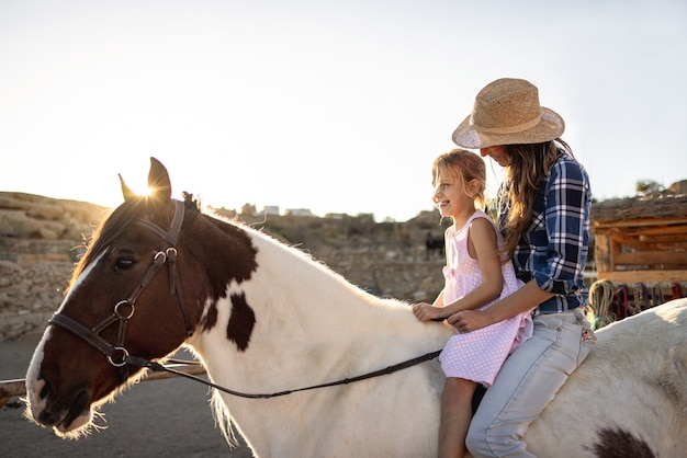 Happy mother and daughter riding a horse at sunset