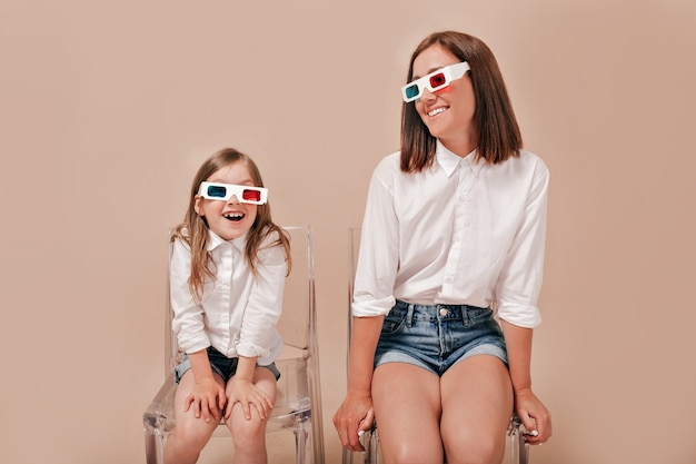 Happy mother and daughter sitting over beige background, having fun and laughing.