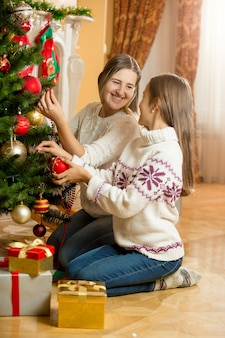 Happy mother and daughter sitting on floor at living room and decorating christmas tree