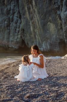 Madre felice e figlia che si siedono insieme e che si guardano in spiaggia in vestito bianco durante il tramonto.