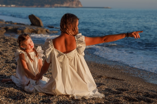 Happy mother and daughter sitting together and looking far in white dress in seashore during sunset .