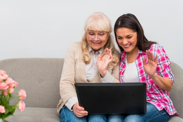 Happy mother and daughter sitting together on sofa doing video chat on laptop