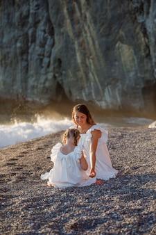Madre felice e figlia che si siedono insieme in vestito bianco in spiaggia durante il tramonto.