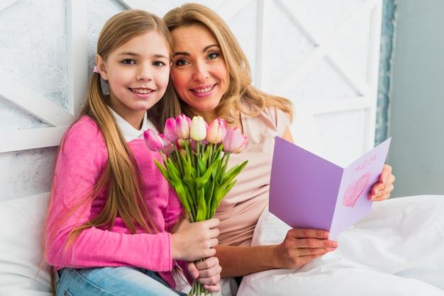 Madre felice e figlia che si siedono con i fiori e la cartolina d'auguri