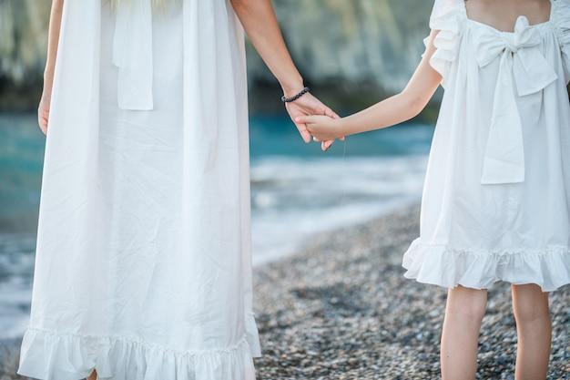 Madre e figlia felici che stanno e che si tengono per mano in vestito bianco in spiaggia durante il tramonto.