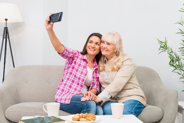 Happy mother and daughter taking selfie on cell phone with breakfast on table