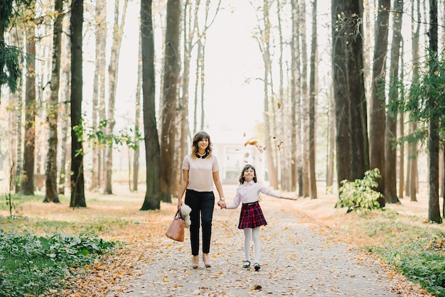 Happy mother and daughter walking in the park