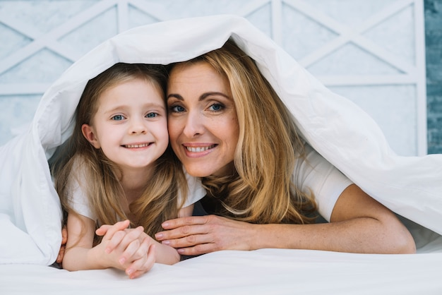 Happy mother and daughter under white blanket