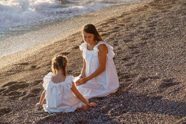 Madre e figlia felici in vestito bianco che si siede sulla sabbia in spiaggia durante il tramonto