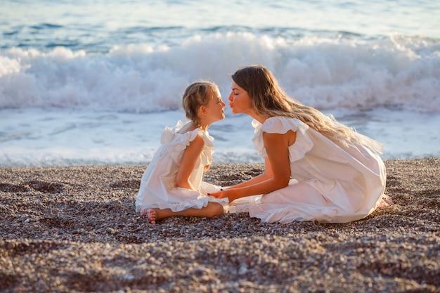 Madre e figlia felici in vestito bianco che si siedono insieme e che si baciano in spiaggia durante il tramonto.