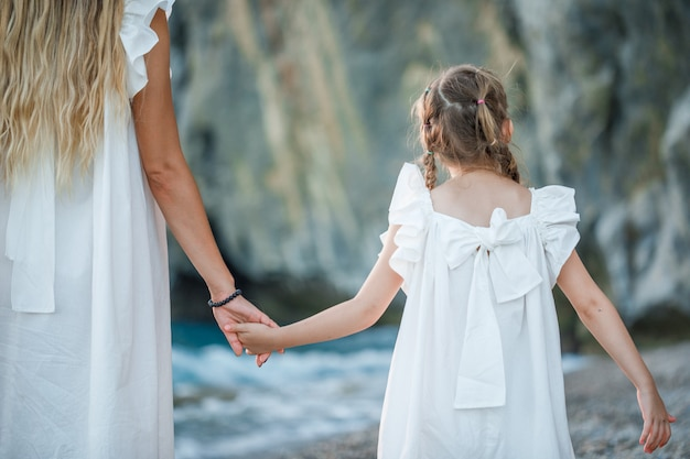 Madre e figlia felici nella condizione del vestito bianco e tenersi per mano in spiaggia durante il tramonto.