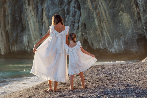 Happy mother and daughter in white dress standing and holding their dresses in seashore during sunset . back view