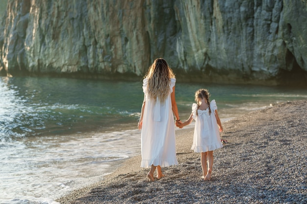 Happy mother and daughter in white dress walking in seashore during sunset. back view
