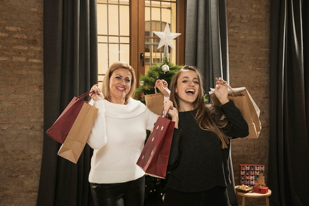 Happy mother and daughter with shopping bags