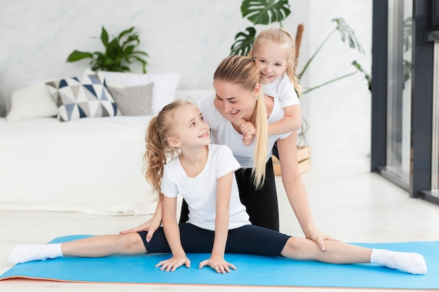 Happy mother and daughters at home on yoga mat