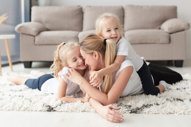 Happy mother and daughters posing at home