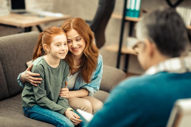 ハッピーマザー。素晴らしい気分で娘に微笑んでいる喜んでポジティブな女性