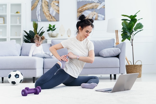 Happy mother doing morning exercises in yoga pose while her little daughter playing at home. young adorable mom having fun practicing meditation relaxing on stress free weekend with baby girl.