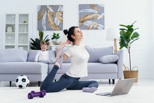 Happy mother doing morning exercises in yoga pose while her little daughter playing at home.