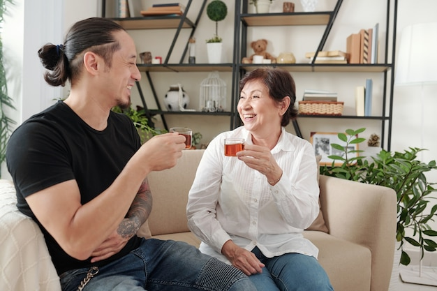 Happy mother drinking tea and laughing during conversation on the sofa with her son in the living room