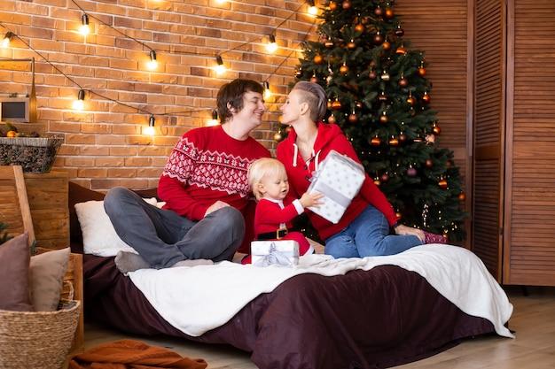 幸せな母、父、そして小さな子供が家のクリスマスツリーの近くで楽しんでいます。休日に一緒に時間を楽しんでいます。