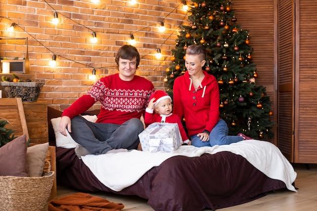 クリスマスツリーの近くで幸せな母、父と小さな子供。休日に一緒に時間を楽しんでいます。メリークリスマス、そしてハッピーニューイヤー。