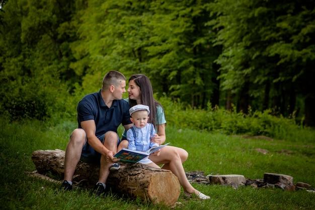 Счастливая мать, отец и сын читают книгу в парке.