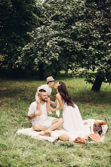 행복 한 어머니, 아버지와 그들의 귀여운 작은 아들 여름 공원에서 피크닉을 데. 그의 아버지 어깨에 앉아 아이. 가족 및 레저 개념