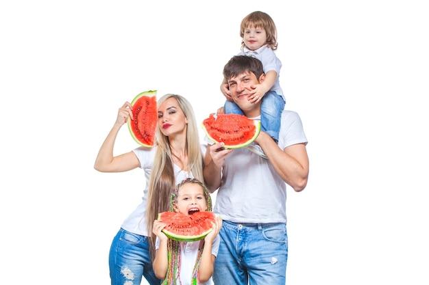 Счастливая мать, отец и их дочь, стоя с кусочками арбуза