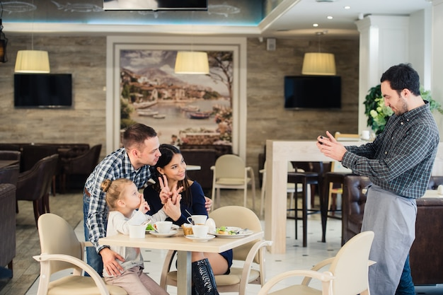 Happy mother, father and little girl having dinner asking waiter to take picture with smartphone