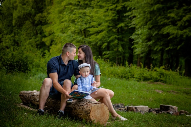 Happy mother, father and son read a book in the park.