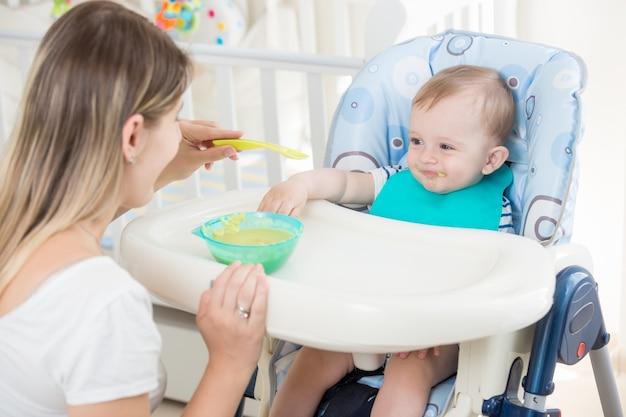幸せな母親が男の子にフルーツソースを与えている