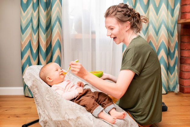 Happy mother feeds laughing baby vegetable puree from a plastic spoon at home.