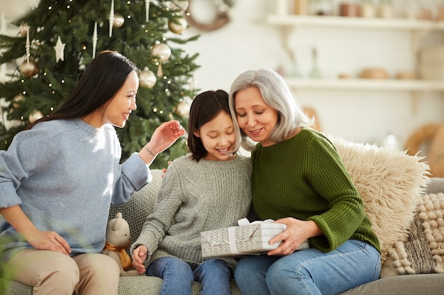 Happy mother getting christmas present from her two daughters they celebrating christmas at home