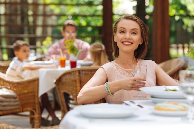 ハッピーマザー。夏のテラスに座っている子供たちを待っている間、素敵な気持ちで幸せな魅力的な母親