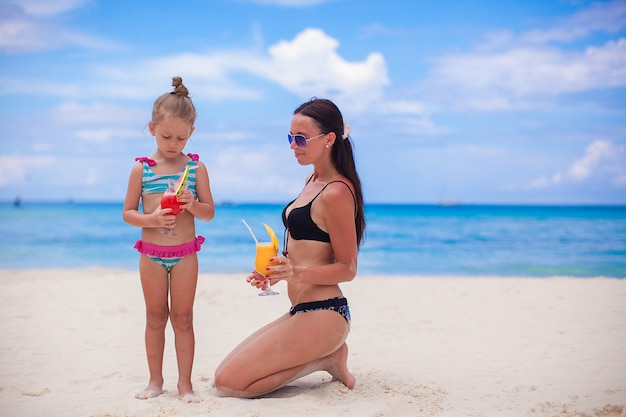 Happy mother and her adorable little daughter with juice at tropical beach