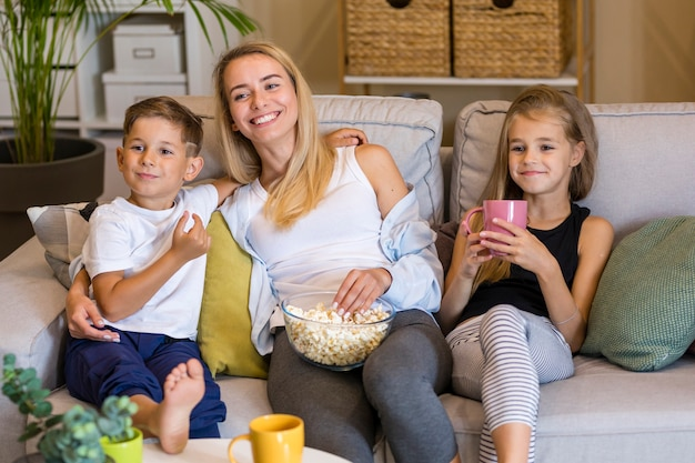 Happy mother and her children eating popcorn