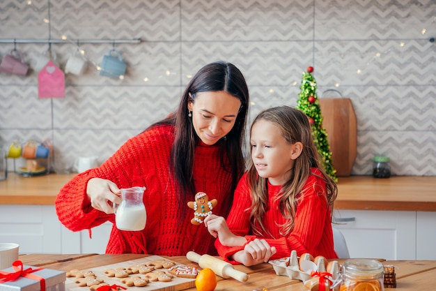 Happy mother and her daughter cooking christmas cookies at kitchen