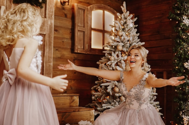 Happy mother and her daughter in pink dresses near the christmas decorations