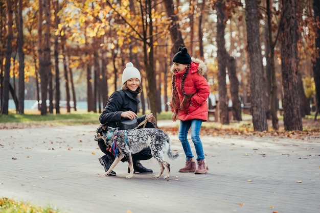 Happy mother and her daughter playing with dog in autumn park