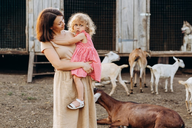 Happy mother and her daughter spend time on an eco farm among goats.